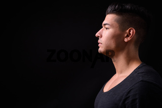 Young handsome multi ethnic man against black background