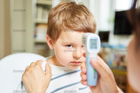 Kinderarzt beim kontaktlos Fieber messen