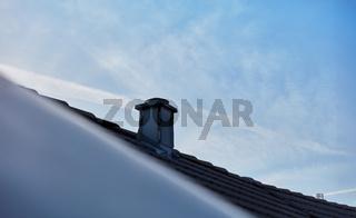 Schornstein auf Dach vor blauem Himmel mit Wolken