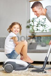 Kind sitzt auf Staubsauger beim Hausputz