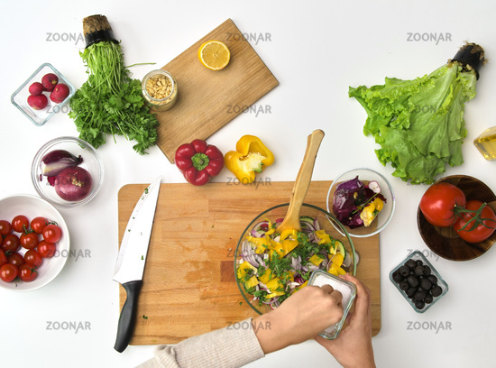 hands cooking vegetable salad on kitchen table
