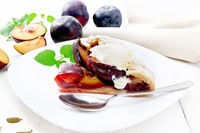 Galeta with plums in plate on light wooden board