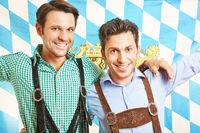 Zwei Männer in Lederhosen mit bayrischer Flagge