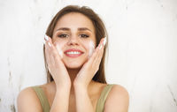 Beautiful young caucasian woman washing her face with foam