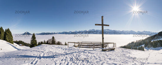 Summit Cross on snow mountain with blue Sky and Sun. Great view to Mountain Range above inversion valley fog layer. Ofterschwanger Horn, Alps, Allgau, Bavaria, Germany.