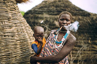TOPOSA TRIBE, SOUTH SUDAN - MARCH 12, 2020: Woman from Toposa Tribe smoking pipe and carrying baby while standing near traditional huts in village in South Sudan, Africa