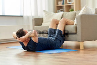 man making abdominal exercises at home