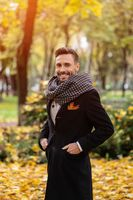 Handsome man wearing dark blue coat and scarf waiting on his date smile on camera. Young freelancer man stands on the street in an autumn coat looking at his woman