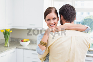 Young couple hugging with woman smiling at camera