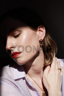 Caucasian young woman with red lips wearing luxury golden jewellery. Vertical close-up of beautiful woman.