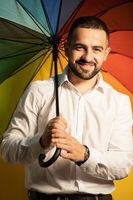 Young straight man with a rainbow umbrella behind his back. Healthy fashion lifestyle, people sincere emotions, cold season concept. Handsome guy in support of LGBTQ society