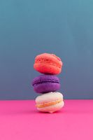 Close up of white, purple and pink macarons stacked on pink and blue background