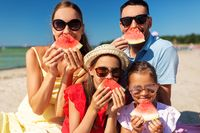 happy family with watermelon on picnic on beach