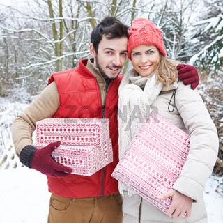 Paar mit Geschenken zu Weihnachten im Schnee