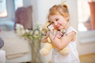 Blondes Kind kuschelt Teddy