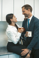 Couple drinking coffee and flirting during lunchtime. Smiling man and woman hold cups of hot drinks looking each other. Office romance concept. High quality photo