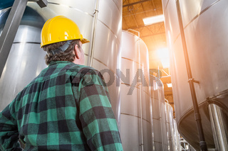 Man Wearing Hard Hat Looking Up At Large Industrial Tanks
