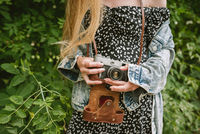 Closeup of woman's hands holding old vintage film camera