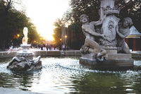 Fountain Alcachofa with sunset in background along path in park Retiro, Madrid, Spain