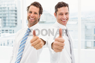 Happy businessmen gesturing thumbs up in office
