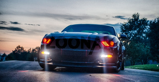 fast american power muscle car at sunset on road