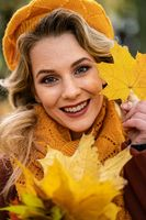 Close up. Young woman in beige knitted beret with autumn leaves in hand and fall yellow garden or park. Beautiful smiling young woman in autumn leaves
