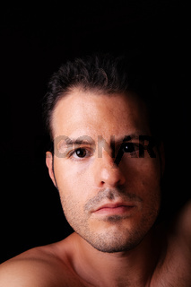 Intimate self portrait of a young man on a dark background.