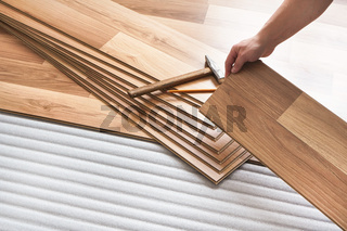 Installing laminated floor, detail on man hands holding wooden tile, over white foam base layer