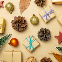 Christmas ornament and gift boxes, pine cones on brown background. flat lay, top view