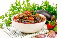Lentils with eggplant in bowl on light board