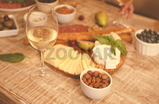 Dinner with snacks and wineglasses on table in living room