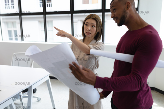 Diverse male and female colleague looking at blueprints and discussing