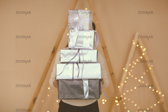 Woman holding wrapped gifts covering face