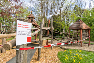 Closed playground with police tape and warning sign (German text: playground closed) due to Corona virus (Covid-19)