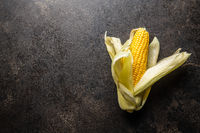 Uncooked corn cob on black table.