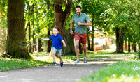 happy father and son compete in running at park