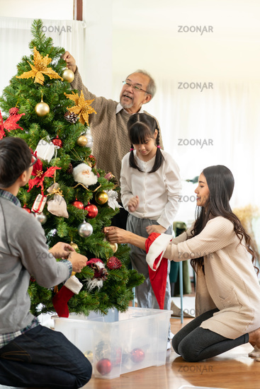 Multigenerational Family decorating a Christmas tree for season greeting.