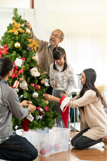 Multigenerational Family decorating a Christmas tree for season greeting.