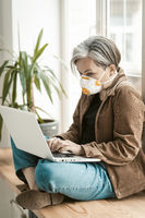 Greying businesswoman works laptop from home. Aged woman wearing protective mask uses mobile internet on computer sitting at windowsill. Qurarantine concept