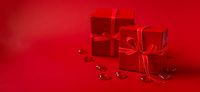 Red gift boxes with red ribbon and decorative hearts on red background