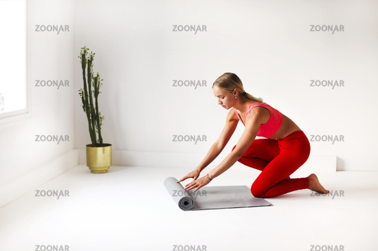 Woman in sportswear preparing mat for yoga lesson