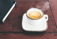 cup of steaming hot espresso on rustic wooden desk
