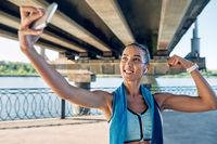 Beautiful sporty woman making selfie flexing her muscles