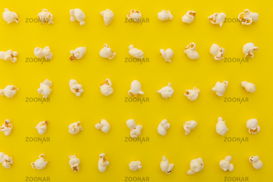 High angle view of popcorn in multiple rows on yellow background