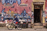 The cyclist in front of the colourful graffiti wall
