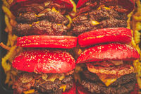 A set of red bun homemade delicious burgers of beef, bacon, cheese, grilled onion on a dark rusty