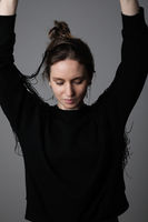 Vertical portrait of young happy woman, dancing with hands up. Isolated.