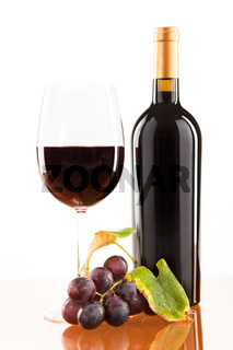 Red wine in glass with bottle and wine grapes