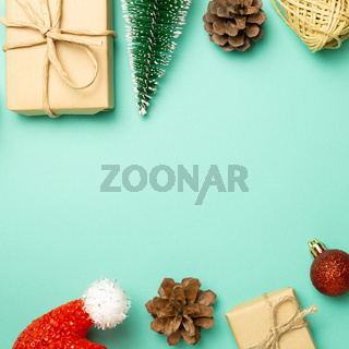 Christmas concept. Gift boxes with fir tree, bauble, pine cones, santa claus hat on green background. flat lay, top view, copy space