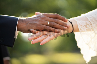 Hands of a dark-skinned groom and light-skinned bride with rings gently touch each other close up View